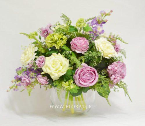 Букет в стеклянной вазе из декоративных цветов и растений.