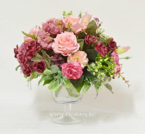 Композиция из декоративных  цветов в стеклянной вазе на ножке.