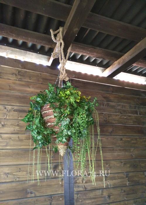 Искусственные растения в подвесной корзине.